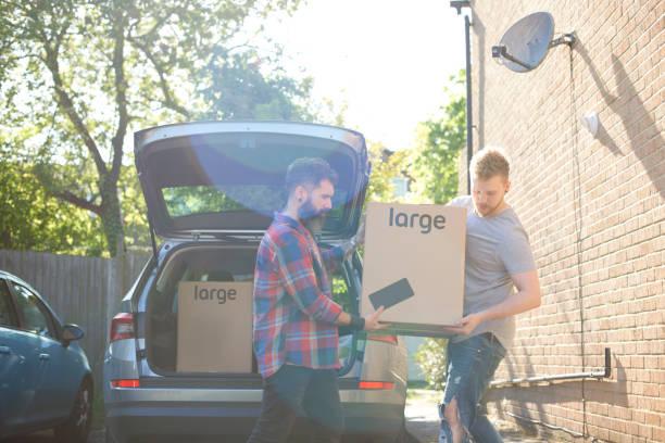 Deux jeunes hommes qui chargent des cartons de déménagement dans le coffre d'une voiture