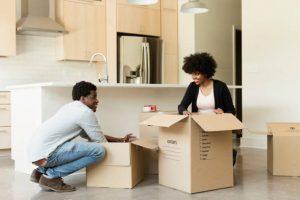 Couple en train de faire ses cartons de déménagement dans la cuisine