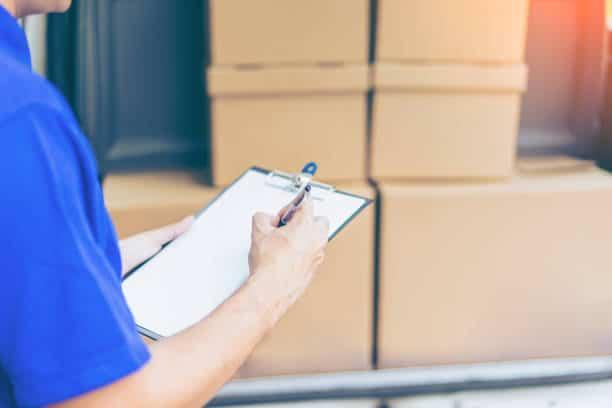 Professionnel du déménagement qui remplit un document devant un camion avec des cartons