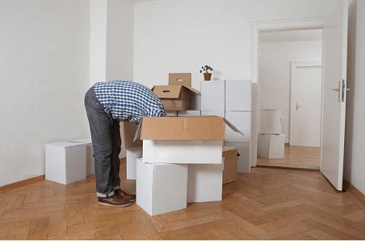 personne la tête dans les cartons de déménagement
